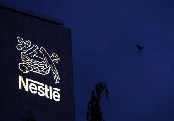 A bird flies past the logo at the headquarters of world food giant Nestle in Vevey October 16, 2014. REUTERS/Denis Balibouse